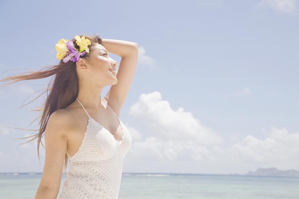ビーチで空を見上げる女性