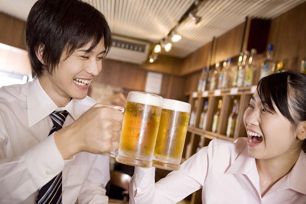 ビールで乾杯するビジネスマンとビジネスレデ