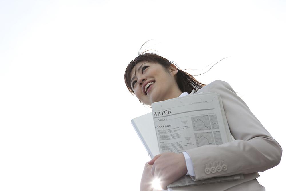 新聞を持って外に立つol