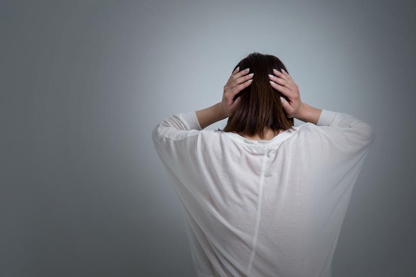 頭を抱えた傷ついた女性