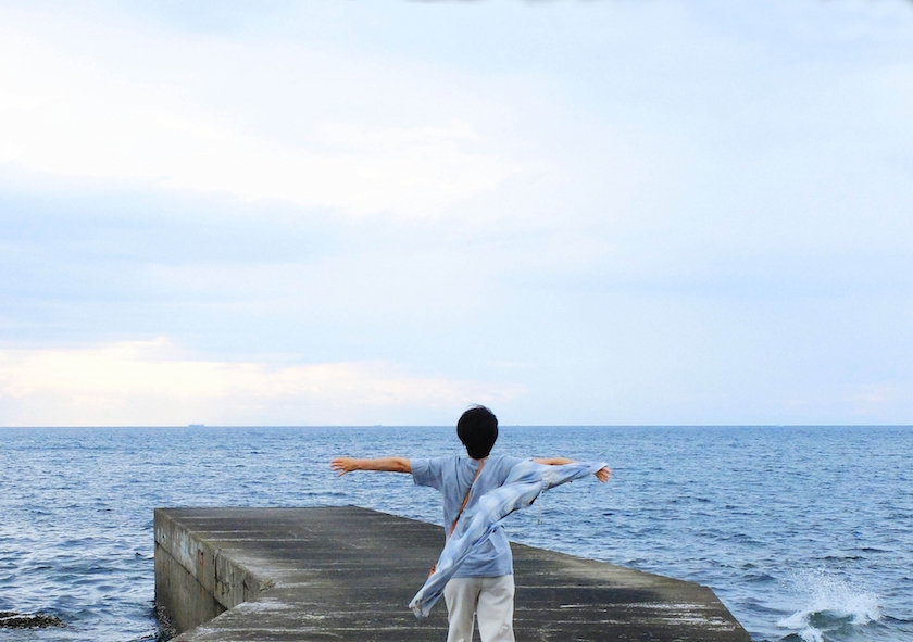 海をみながら深呼吸する女性